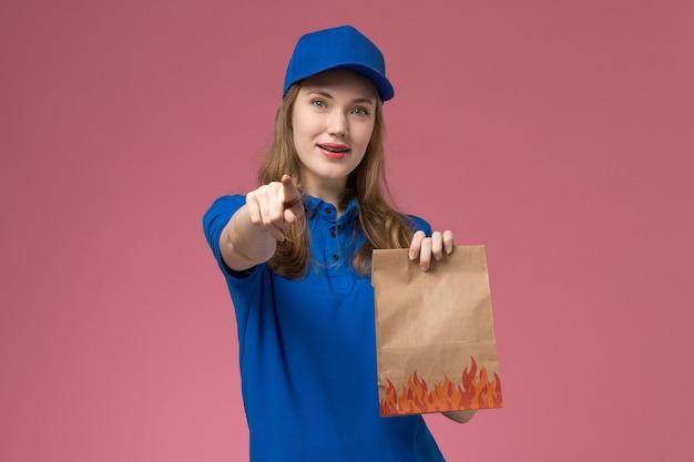 Mensajero femenino de vista frontal en uniforme azul sosteniendo el paquete de alimentos con una leve sonrisa señalando en la empresa de uniforme de servicio de trabajador de trabajo de escritorio rosa claro