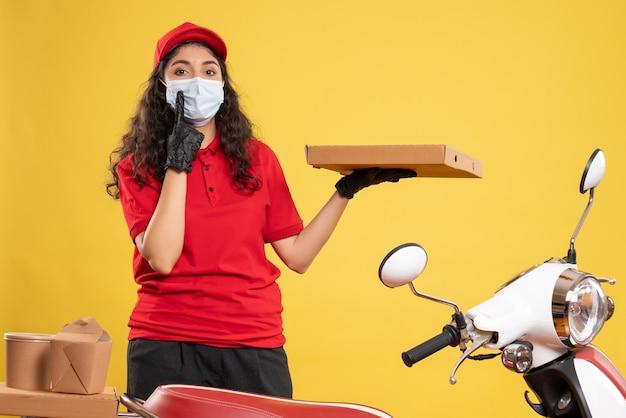 Mensajero femenino de vista frontal en uniforme rojo con caja de pizza en el fondo amarillo trabajador de servicio covid- entrega de trabajo de virus pandémico