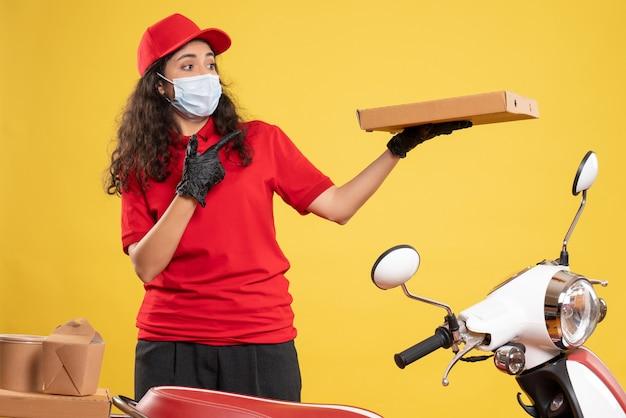 Mensajero femenino de vista frontal en uniforme rojo con caja de pizza sobre fondo amarillo servicio covid- entrega de trabajo de virus pandémico