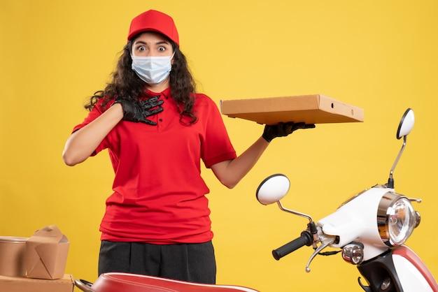 Mensajero femenino de vista frontal en uniforme rojo con caja de pizza sobre fondo amarillo servicio trabajador covid- entrega de trabajo de virus