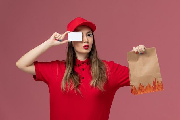 Mensajero femenino de vista frontal en uniforme rojo con paquete de comida de tarjeta blanca sobre fondo rosa claro servicio trabajo entrega uniforme empresa