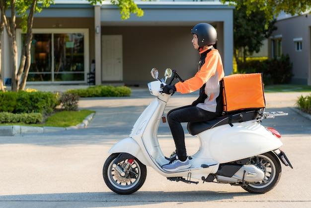 Mensajero de hombre asiático en scooter que entrega comida en las calles de la ciudad con una entrega de comida caliente desde comida para llevar y restaurantes hasta casa, entrega de comida rápida y concepto en línea de compras.