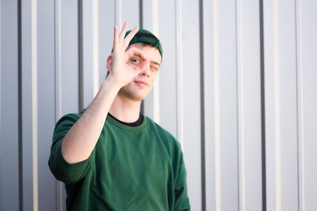 Mensajero joven en la ropa verde que muestra gesto aceptable