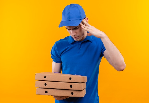 Mensajero joven con uniforme azul y gorra azul confundido