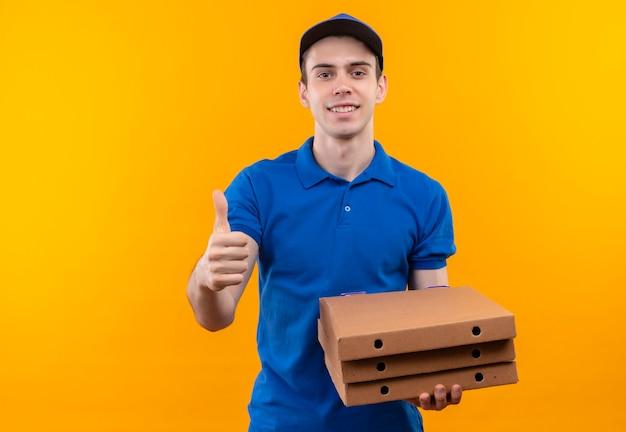 Mensajero joven con uniforme azul y gorra azul haciendo feliz pulgar hacia arriba