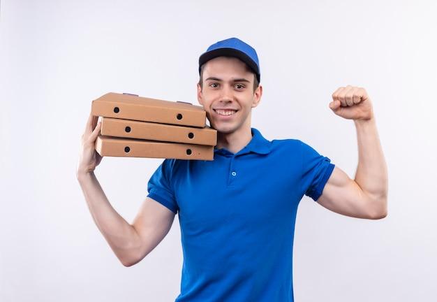 Mensajero joven con uniforme azul y gorra azul haciendo feliz puño y sosteniendo cajas