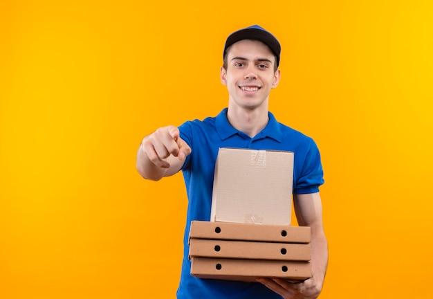Mensajero joven vestido con uniforme azul y gorra azul felizmente apunta y sostiene cajas