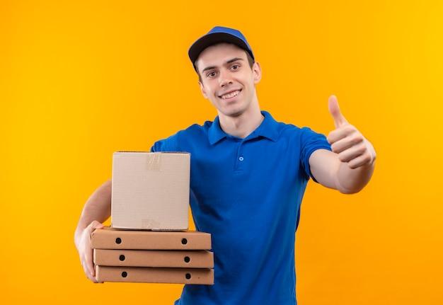 Mensajero joven vistiendo uniforme azul y gorra azul haciendo feliz pulgares arriba sostiene cajas