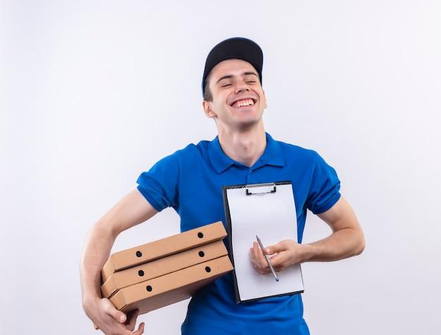 Mensajero joven vistiendo uniforme azul y gorra azul se ríe y sostiene bolígrafo portapapeles y bolsas