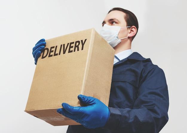 Mensajero masculino con una caja en una máscara protectora y guantes. entrega a domicilio de alimentos y medicamentos durante una pandemia covid-19.