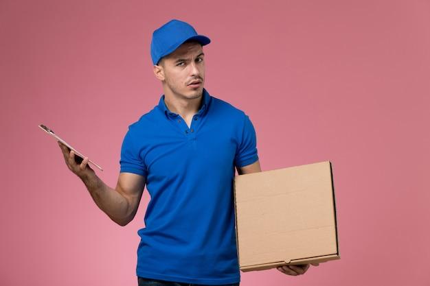 Mensajero masculino en uniforme azul con caja de comida y bloc de notas en rosa, trabajador de entrega de servicio uniforme de trabajo