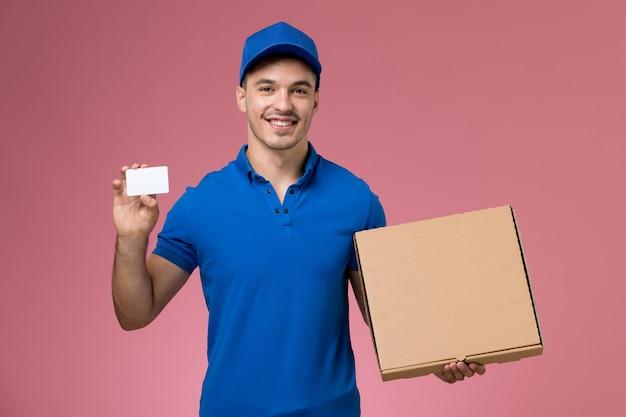 Mensajero masculino en uniforme azul con caja de comida y tarjeta en rosa, trabajador de entrega de servicio uniforme