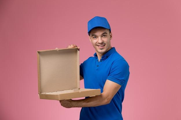 Mensajero masculino en uniforme azul sosteniendo y abriendo la caja de comida en rosa, entrega de trabajo de servicio uniforme