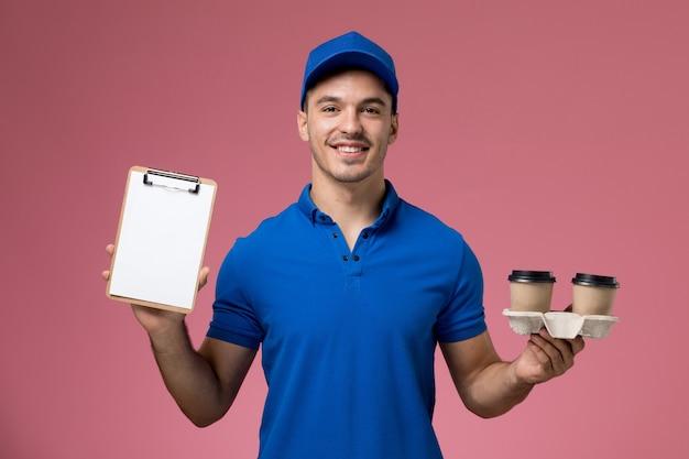 Mensajero masculino en uniforme azul sosteniendo tazas de café de entrega y bloc de notas con sonrisa en rosa, entrega de servicio uniforme