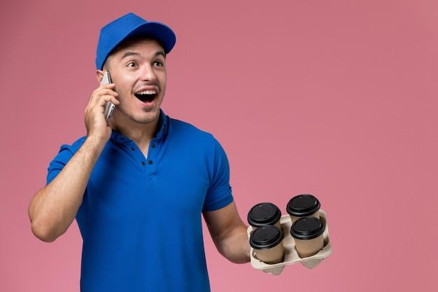 Mensajero masculino en uniforme azul sosteniendo tazas de café de entrega hablando por teléfono en rosa, entrega de trabajo de servicio uniforme
