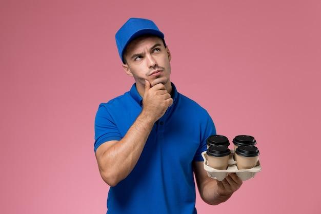 Mensajero masculino en uniforme azul sosteniendo tazas de café marrón pensando en rosa, entrega de servicio uniforme de trabajador