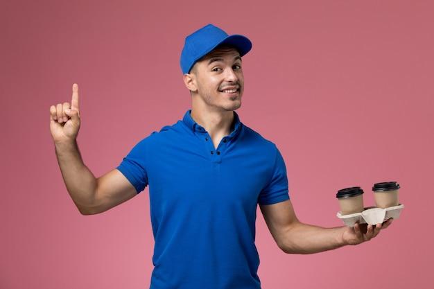 Mensajero masculino en uniforme azul sosteniendo tazas de café sonriendo en rosa, entrega de servicio uniforme de trabajador