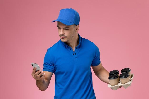 Mensajero masculino en uniforme azul sosteniendo tazas de café usando su teléfono en rosa, entrega de servicio uniforme