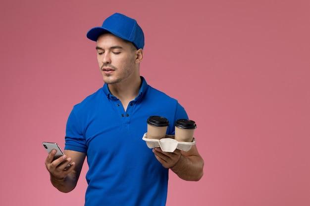 Mensajero masculino en uniforme azul sosteniendo tazas de café y usando su teléfono en rosa, entrega de trabajo uniforme