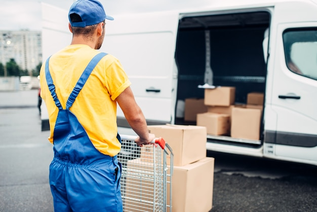 Mensajero masculino en uniforme trabaja con carga, vista posterior. camión con paquetes