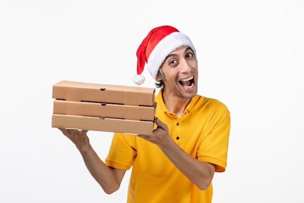 Mensajero masculino de vista frontal con cajas de pizza en la entrega de servicio uniforme de pared blanca