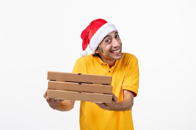 Mensajero masculino de vista frontal con cajas de pizza en la entrega de servicio uniforme de trabajo de pared blanca