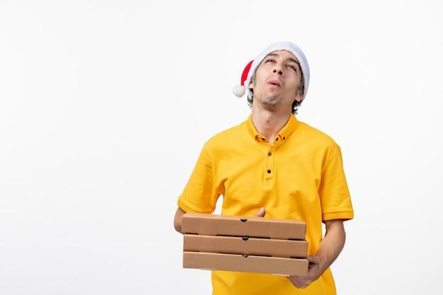 Mensajero masculino de vista frontal con cajas de pizza en servicio de entrega de trabajo uniforme de pared blanca