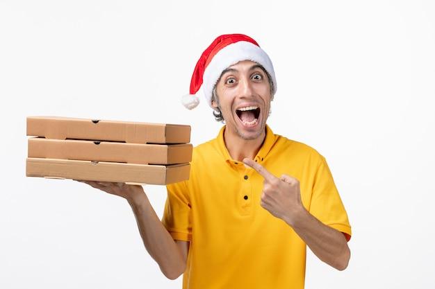 Mensajero masculino de vista frontal con cajas de pizza en servicio de entrega uniforme de pared blanca
