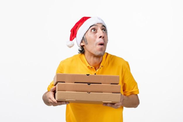 Mensajero masculino de vista frontal con cajas de pizza en servicio de entrega uniforme de trabajo de pared blanca
