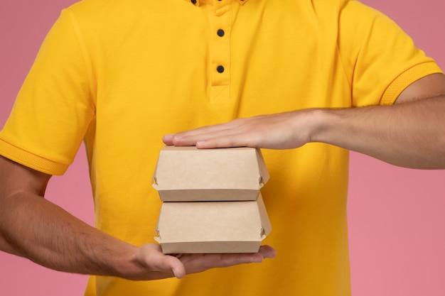 Mensajero masculino de vista frontal cercana en uniforme amarillo y gorra con pequeños paquetes de comida de entrega en sus manos en la pared rosa