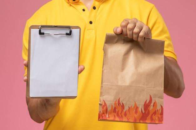 Mensajero masculino de la vista frontal cercana en uniforme amarillo sosteniendo el bloc de notas y el paquete de alimentos en el escritorio rosa
