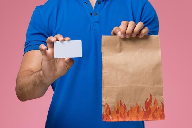Mensajero masculino de vista frontal cercana en uniforme azul con paquete de alimentos y tarjeta en la entrega de trabajo de servicio uniforme rosa