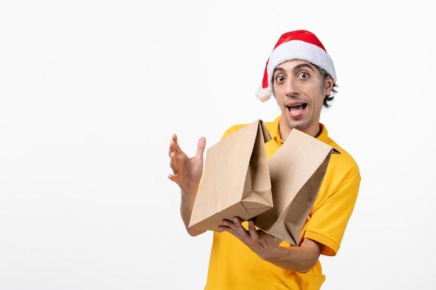 Mensajero masculino de vista frontal con paquetes de alimentos en el piso blanco entrega uniforme de servicio