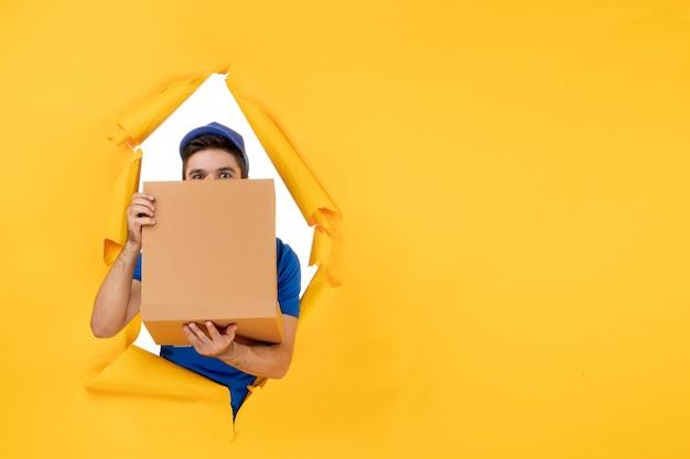 Mensajero masculino de la vista frontal que sostiene la caja de la pizza en el espacio amarillo