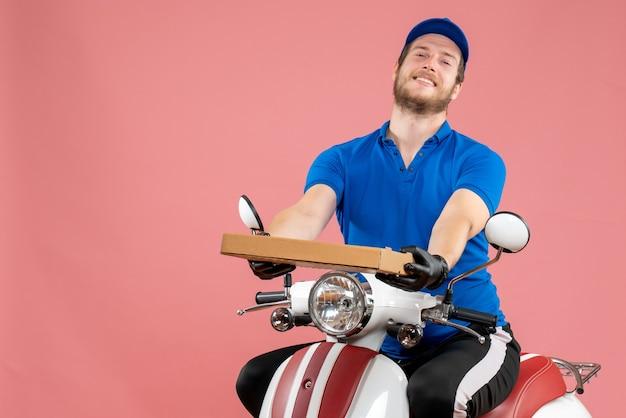 Mensajero masculino de vista frontal sentado en bicicleta y sosteniendo la caja de pizza en el rosa