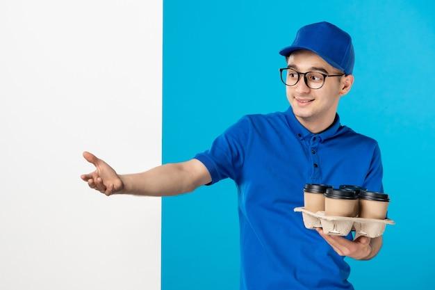 Mensajero masculino vista frontal con tazas de café en azul