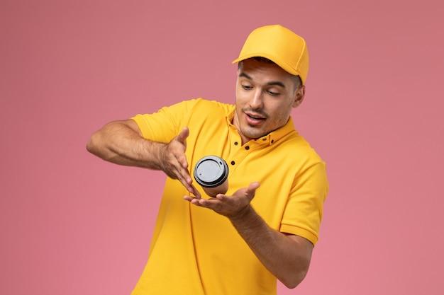 Mensajero masculino de vista frontal en uniforme amarillo apenas sosteniendo la taza de entrega de café marrón sobre el fondo rosa