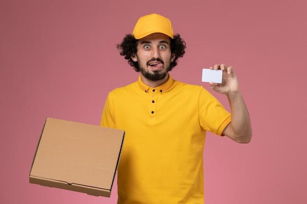 Mensajero masculino de vista frontal en uniforme amarillo con caja de entrega de alimentos y tarjeta en la pared rosa