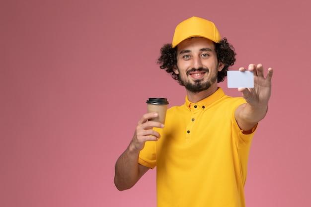 Mensajero masculino de vista frontal en uniforme amarillo y capa sosteniendo la taza de café de entrega y la tarjeta en la pared rosa