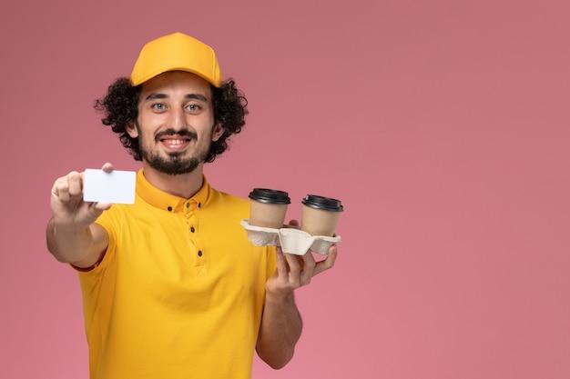 Mensajero masculino de vista frontal en uniforme amarillo y capa sosteniendo tazas de café de entrega marrón y tarjeta en la pared rosa