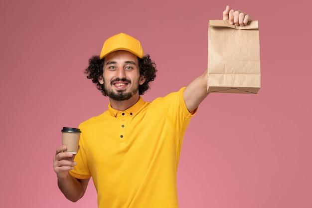 Mensajero masculino de vista frontal en uniforme amarillo y capa con taza de café de entrega y paquete de comida en la pared rosa