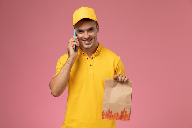 Mensajero masculino de vista frontal en uniforme amarillo sonriendo hablando por teléfono sosteniendo el paquete de alimentos en rosa