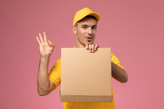 Mensajero masculino de vista frontal en uniforme amarillo sosteniendo y abriendo la caja de entrega de alimentos en el fondo rosa claro