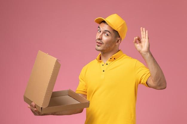 Mensajero masculino de vista frontal en uniforme amarillo sosteniendo y abriendo la caja de entrega de alimentos vacía en el escritorio rosa