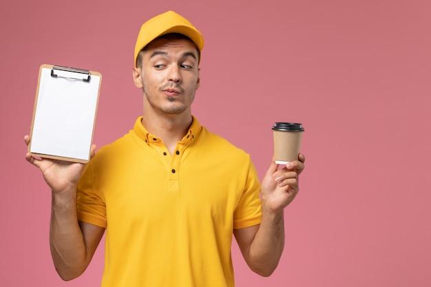 Mensajero masculino de vista frontal en uniforme amarillo sosteniendo la taza de café de entrega y el bloc de notas en el fondo rosa