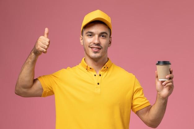 Mensajero masculino de vista frontal en uniforme amarillo sosteniendo la taza de entrega de café en el fondo rosa