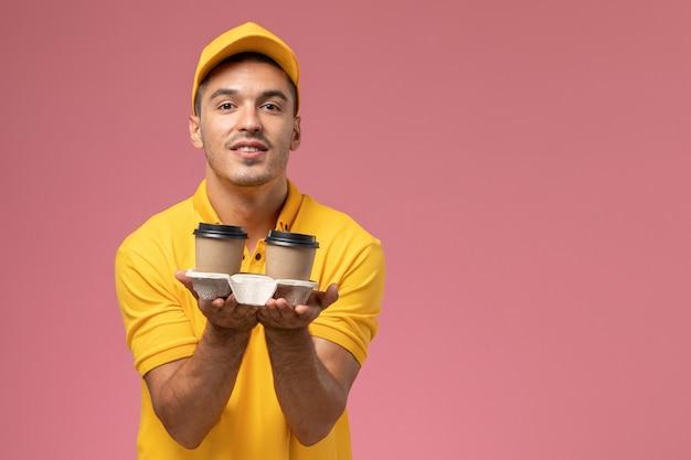 Mensajero masculino de vista frontal en uniforme amarillo sosteniendo tazas de café de entrega en el escritorio de color rosa claro