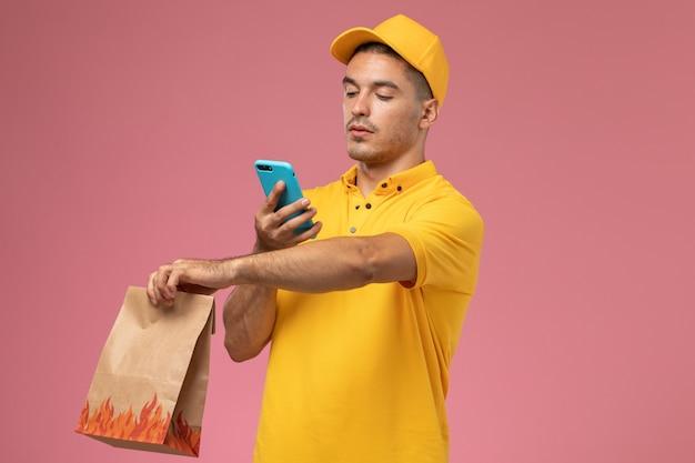 Mensajero masculino de vista frontal en uniforme amarillo usando su teléfono mientras sostiene el paquete de alimentos en el escritorio rosa