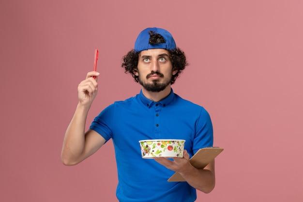 Mensajero masculino de vista frontal en uniforme azul y capa con bolígrafo y tazón de entrega redondo en pared rosa