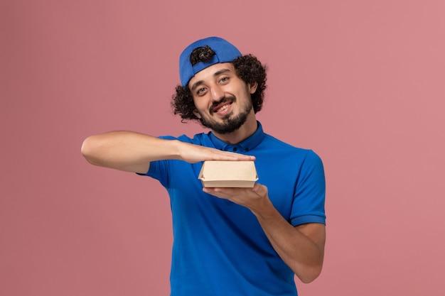 Mensajero masculino de vista frontal en uniforme azul y capa con pequeño paquete de comida de entrega sonriendo en la pared rosa